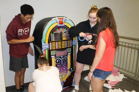 Sophomores Isaac Martin, Jamie Fadgen, Natalie Scchantz, and Amanda Wardlow work together to create a colorful, old-fashioned juke box decoration.
