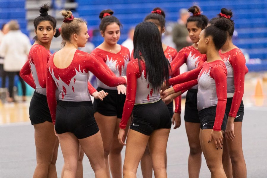 Varsity+gymnastics+huddles+together+at+the+Regional+competition+on+February+5th.+%0A%0A