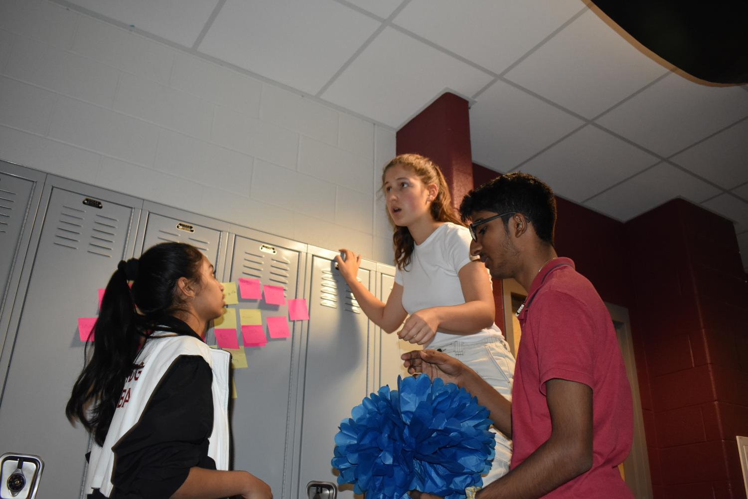"""Sophomore Anurag Gottipati helps decorate her  class hallway. Gottipati is an SCA representative for the sophomore class and was helping decide how to decorate the middle of the hallway. Gottipati explains the plans for the hallway, """"We're trying to make the rocket right now, and we are covering the ceilings with black paper so we can prevent any light from coming in because we're trying to mimic space."""""""