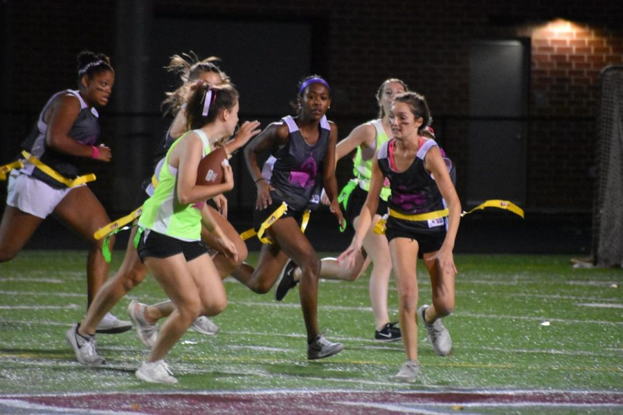 Sprinting with the ball in her hand, senior Chloe Morro, surrounded by junior opponents Jade Laudermilk (left) and Sophia Clarke (right), successfully carries the ball to the endzone, scoring a touchdown for the senior team.