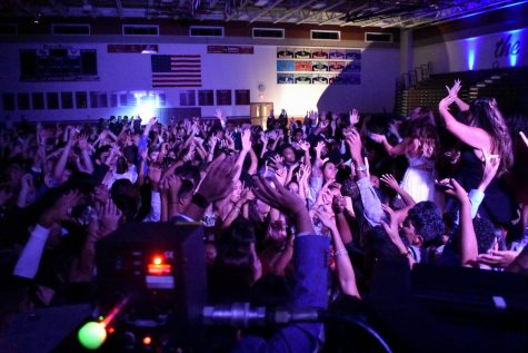 "Waving their hands, homecoming-goers dance along to Miley Cyrus' ""Party in the U.S.A."""