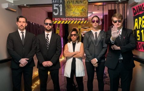 "English teachers Sean Heron, Tyler Anderson, Johanna Ayala-Walsh, Shelby Whittington, and Samuel McClain dress up with the theme of ""Men in Black"" for Space out day. McClain held out his hand to keep anyone from entering Area 51."