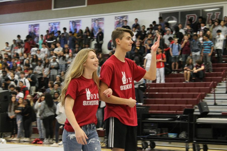 "Seniors Chris Canfield and Kendra Yetter wave to the crowd at the Homecoming pep rally. Canfield and Yetter were voted onto the Homecoming court by peers for the class of 2020. ""It was fun to represent the senior class and all my friends who voted for me,"" Yetter said."