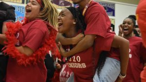 Senior Kayla Davis screams with senior Jordan Cox on her back during the pep rally. Davis was participating with other seniors in the class cheer of the pep rally.