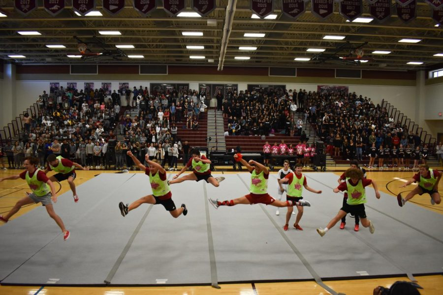 The powderpuff cheerleaders jump into a split in the air while performing. They performed for the pep rally after their game on October 7.