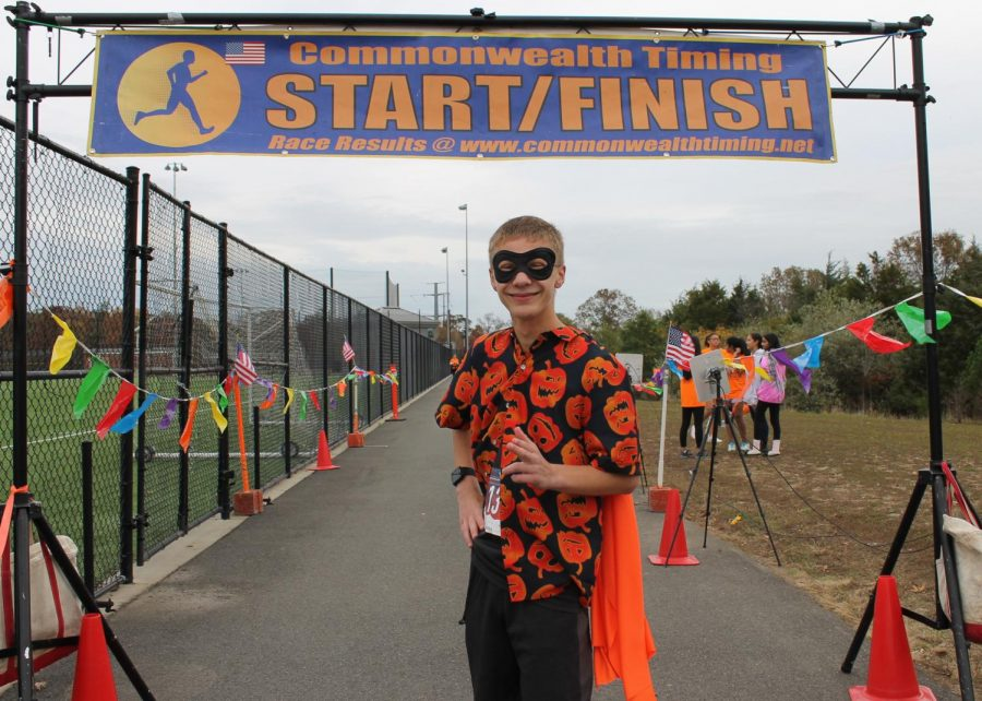 """Freshman Jett Cooper poses in front of the 5k finish line. Cooper was awarded first place winner at the Haunted 5K. """"I felt pretty good. It was tiring, definitely, but I'm proud of what I did,"""" Cooper said."""