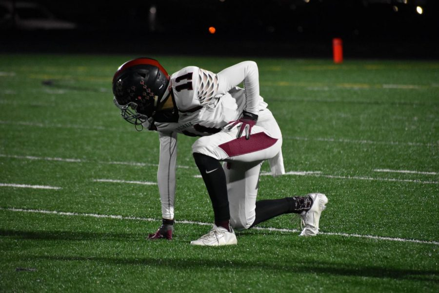 """Senior Rayyan Saleh kneels as he gets ready for his next play. """"At the end of the game, it was kind of sad, because it was my last game,"""" Saleh said."""