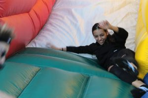 Freshman Julia Freeman slides into the bouncy obstacle course at the tailgate, which was sponsored by SCA.