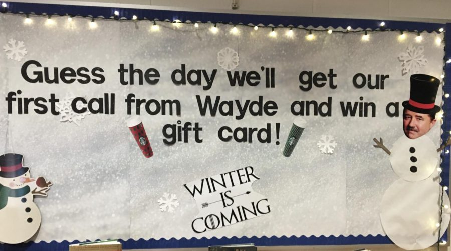 """Guess the day we'll get our first call from Wayde and win a gift card!"" a sign reads, decked out with a Wayde-faced snowman and lights in the RRHS library. In front of the sign sits the box for students to place their guesses for the 'Game of Phones.'"