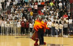 Rocky and former physics teacher Myron Hanke spread the holiday cheer as they share a hug during Hanke's lip-sync performance. The students were on their feet as he continued to saunter around the gym to the beat of the song.