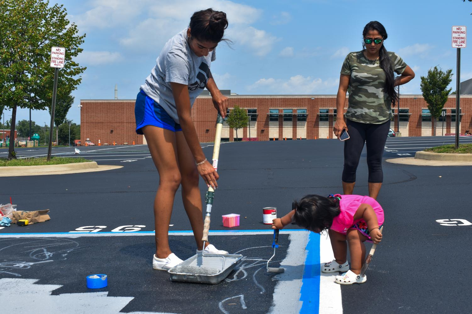 Senior Gabby Lozada rolls gray paint on her spot with her family.