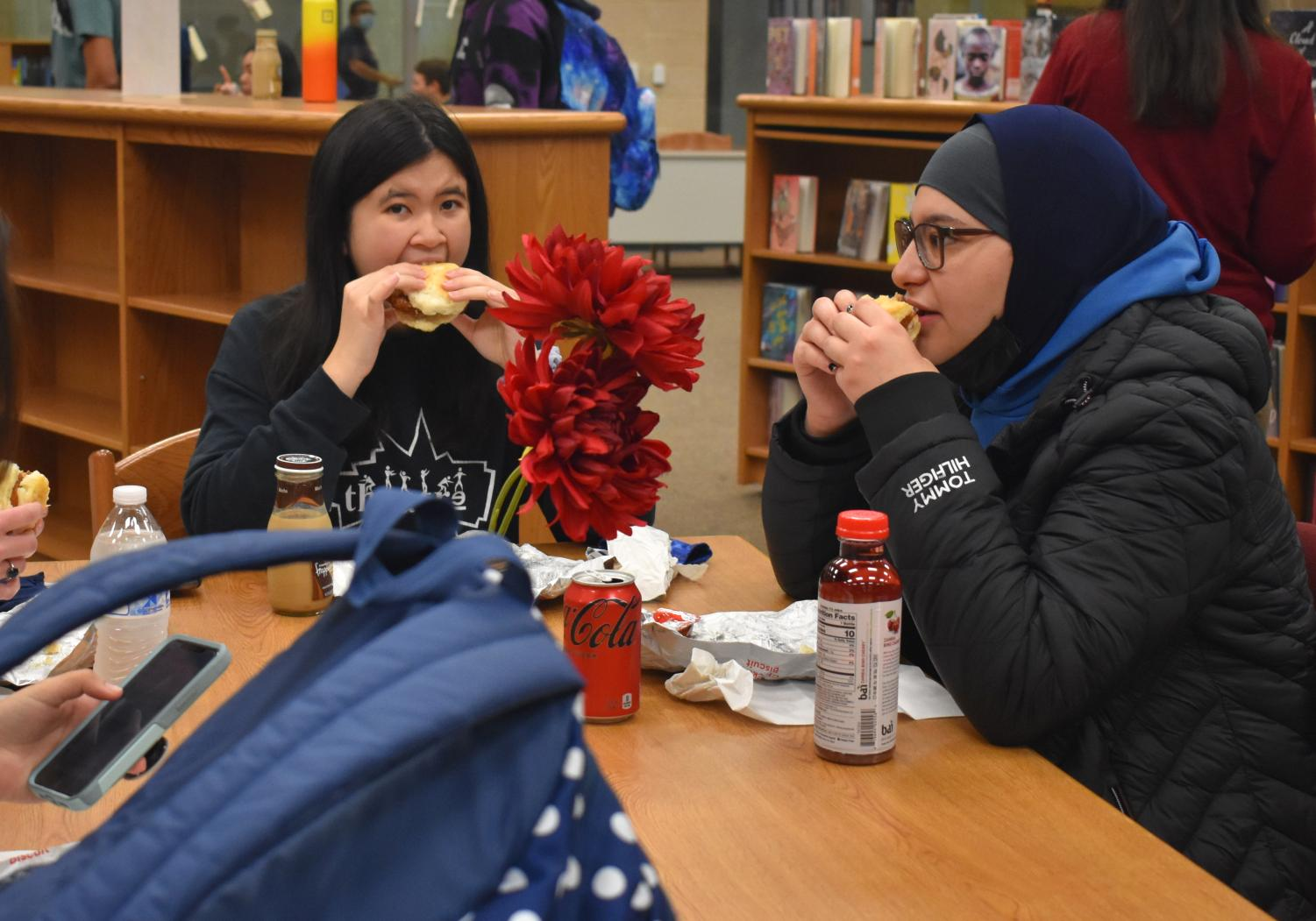 """Seniors Esther McPalmer and Maryam Nabih eat Chick-fil-A breakfast sandwiches in the library during senior breakfast. """"[Senior year] is going OK, it's not bad, and I'm enjoying early release and [taking] less classes,"""" McPalmer said. McPalmer looks forward to prom and future senior breakfasts during her last year of high school."""